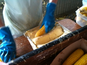 Buttering corn at the Sun Prairie Sweet Corn Festival